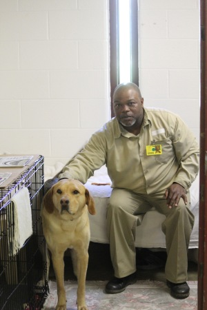 Mike Wathal sits in his cell with Bruce, a 2-year-old shelter dog and German Shepherd mix. Wathal and Bruce have been working together for five weeks.